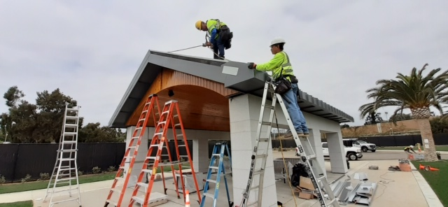 Two roofers from Modern Roofing installing a metal roof on a pavilion in 2020